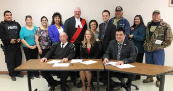 Ogimaa Duke Peltier met with Wikwemikong Tribal Police Chief Gary Reid and Crown Attorney Stacy Haner to sign the Wikwemikong Justice Diversion Protocol last week. The protocol  outlines the process of pre-charge and post-charge diversion where the police and Crown Attorney can refer cases to the Wikwemikong Peacemaker Justice Program to hold justice circles.  Also present were justice personnel and members of the Wikwemikong Justice Committee: In photo are, front row, from left, Wikwemikong Police Chief Gary Reid, Crown Attorney Stacy Haner, Ogimaa Duke Peltier, back row, Detective Constable Scott Cooper, Miranda Trudeau, Rhonda Trudeau, Band Councillor Gladys  Wakegijig, Justice R.P. Villeneuve, Dorothy Fox, Crown Attorney Jeremy Schaffer, Raymond Jackson, Lora Mackie and Howard Trudeau. photo by  Marilyn Jacko