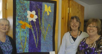 Barb Bright, left, Jan Bainbridge and Charlene Chambers pose with the wall hanging they designed and quilted for the Quilt Show held this past weekend. Proceeds from the show go towards the purchase of daffodils for the festival.