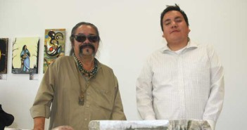 Artist curator Mike Cywink and arts intern Andrew Manitowabi with pieces by Albert Mishinijima and Nick Cywink.