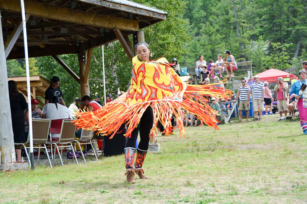 This fancy shawl dancer is all ablaze in her fire-motif shawl and moccasin tops.