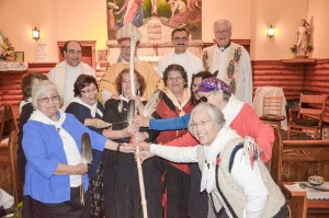 Members of the Diocesan Order of Service grasp the bishop's mitre as they welcome Dianne Musgrove as the newest member of their order to the fold as local Jesuit priests and Bishop Jean Louis Plouffe look on.