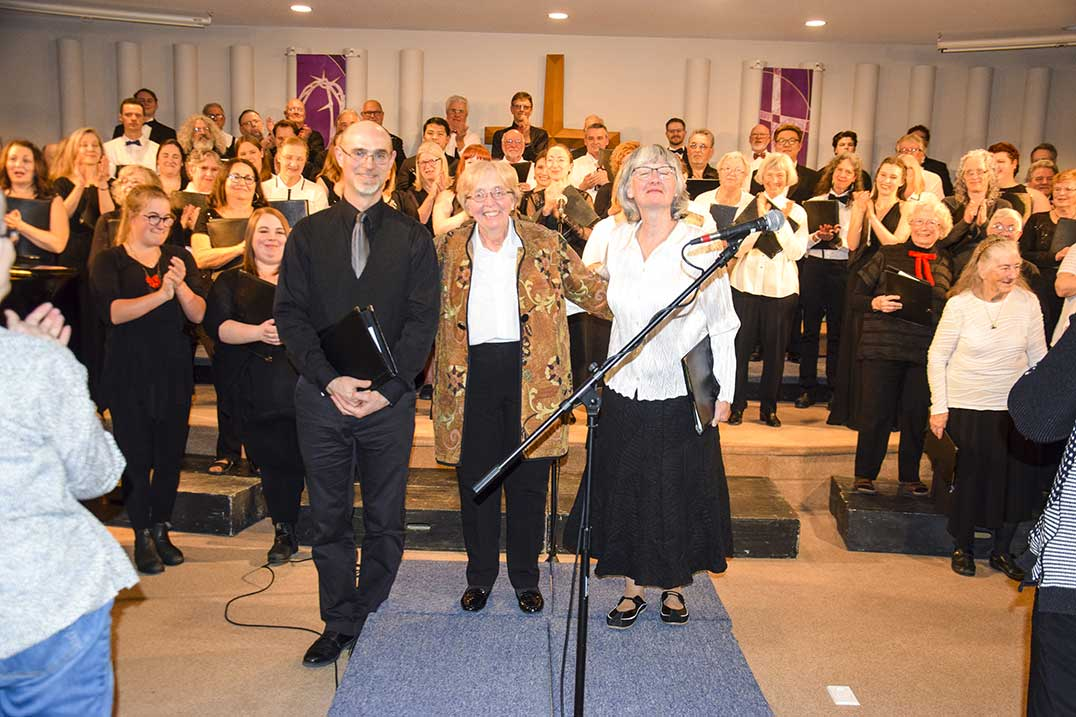 Three conductors, Chris Theijsmeijer of the Island Singers, Lydia Adams of the Elmer Isleler Singers and Jane Best of the Manitoulin Community Choir acknowledge the applause following the final performance of the JUNOAward winning choral group the Elmer Iseler Singers at the Mindemoya Missionary Church. Members of the three choirs are all smiles as they stand behind their conductors. photo by Michael Erskine