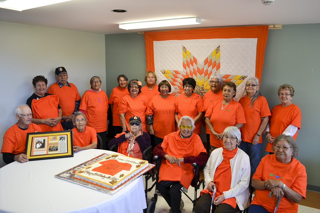 Indian Residential School survivors at the Celebration of Life held last week at the Anishinaabemowin Gamig Elder's Centre in M'Chigeeng pose for a group photo wearing orange t-shirts in support of Orange Shirt Day. photo by Robin Burridge