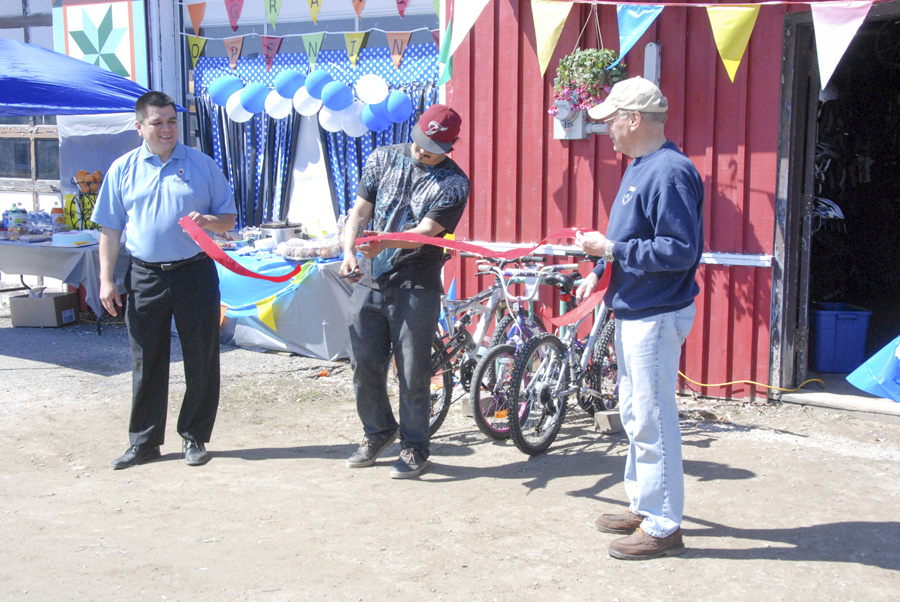 Josh Shaw gets a helping hand from, left, Wikwemikong Chief Duke Peltier and, right, Assiginack Reeve Paul Moffat during the ribbon cutting ceremony.