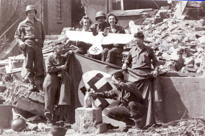 Blair holding the left end of the German flag. He found the small dog in a house and carried it with him in his jacket until the end of the war.