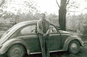John Hodder poses in front of his first car a VW, May 1962 during his first year of teaching at Little Current Public School.