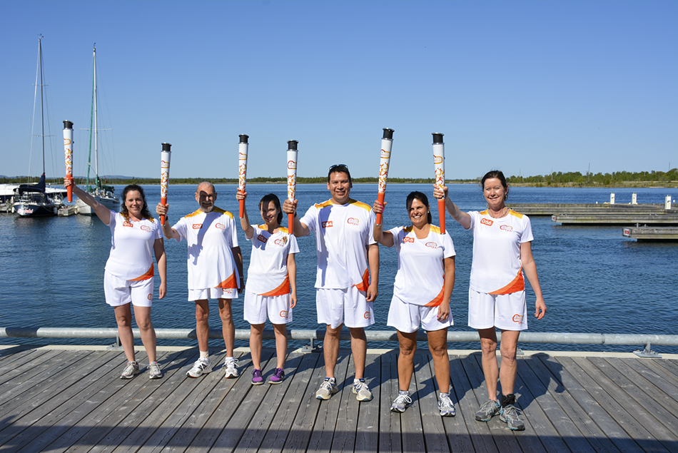 From left, Manitoulin Pan Am Torch Relay torchbearers Alicia McCutcheon, Ivan Wheale, Lauren  Abotossaway, Ed Simon, Lisa Winkel and Kelly O'Hare stand on the Little Current docks.