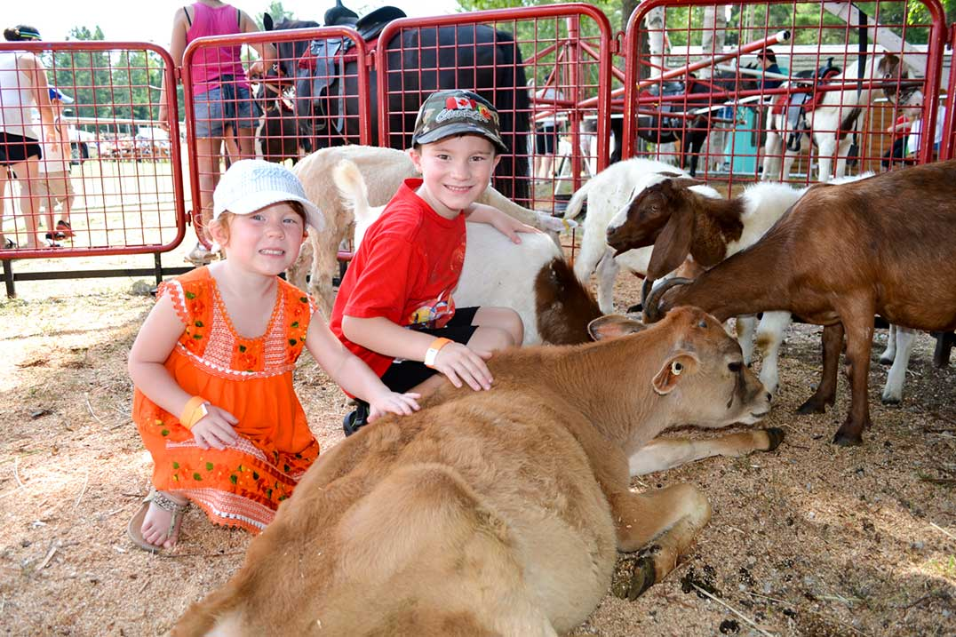 Emily Watt, age 4, and Colin Watt, age 6, from Toronto enjoy the  petting zoo during their visit to Manitoulin Island and the Providence Bay Fair.