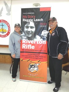 Reggie Leach and his daughter Brandie pose in front of a banner promoting his book at the official launch in his home town of Riverton.