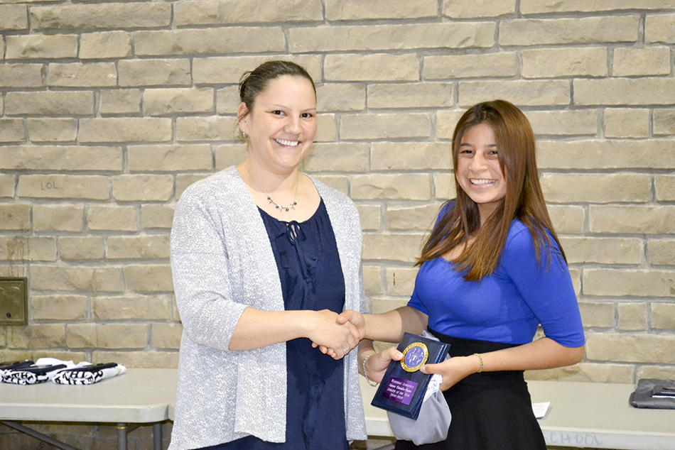 Wikwemikong High School athletic director Jillian Peltier presents Aurora Ominika-Enosse with the female Athlete of the Year Award.