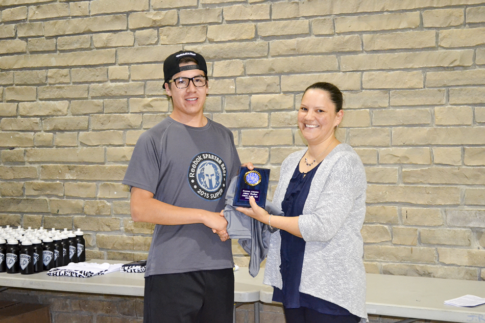 Wikwemikong High School athletic director Jillian Peltier presents Adrian Trudeau with the male Athlete of the Year Award.
