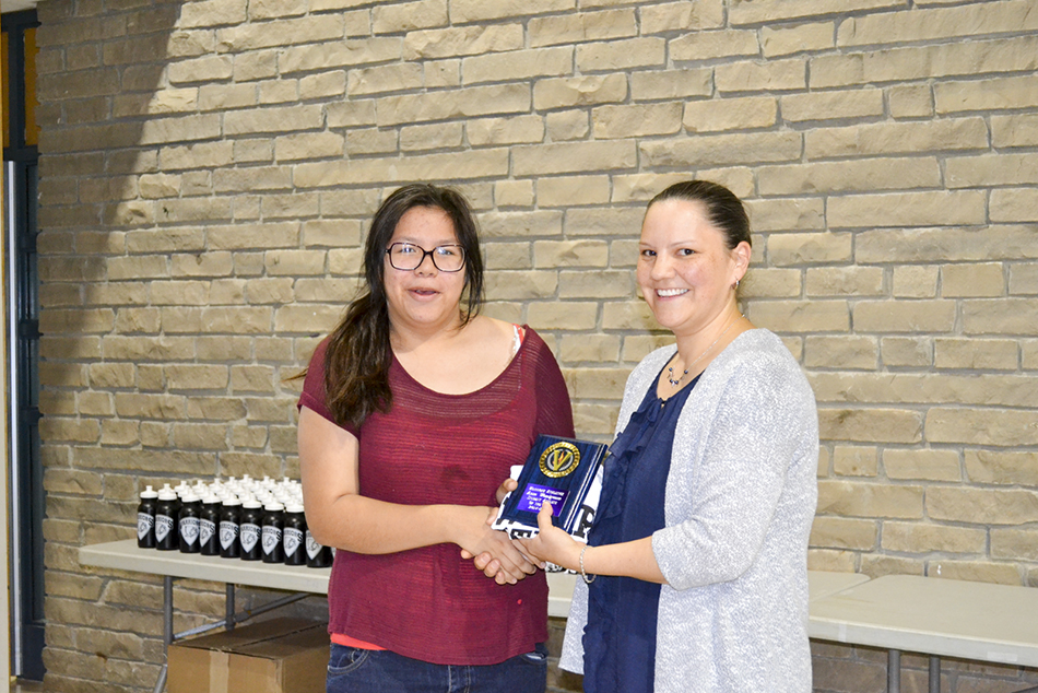 Annie Wemigwans receives the Student Athlete of the Year Award from Wikwemikong High School athletic director Jillian Peltier.