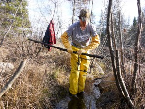 A youth trapper carefully prepares to set a trap in a wetland. The weather was unseasonably warm and he had to remove his coat during this exercise.