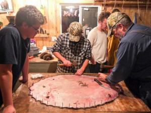 The youth trappers work with Mr. Hagen learning how to stretch a beaver pelt.