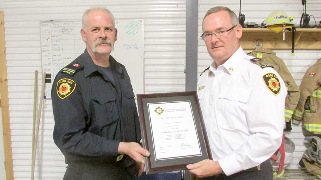 Gore Bay firefighter John Baker, left, is presented with a Company Officer Level No. 1 certificate, by Gore Bay Fire Chief Mike Addison.