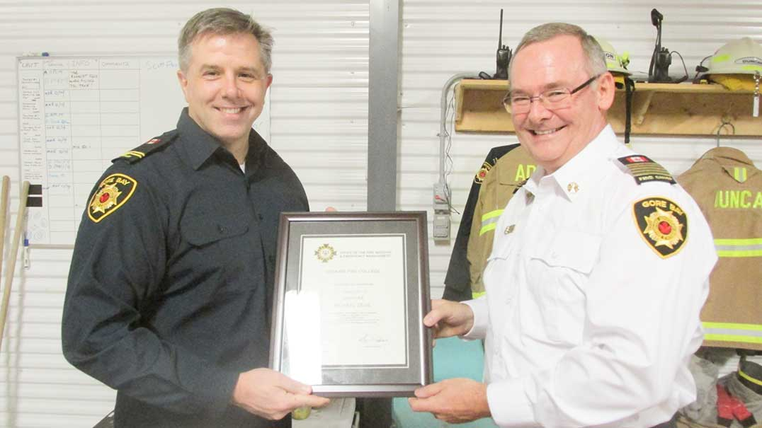 Mike Addison, fire Chief of the Gore Bay Joint Fire Department, right, presents a Company Officer Level No. 1 certificate to firefighter Mike Zegil.